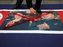 An activist from an anti-North Korea civic group defaces a North Korea flag depicting North's leader Kim Jong-un and his wife Ri Sol-ju during a rally against North Korea's nuclear test near the U.S. embassy in central Seoul