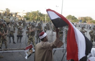 A supporter of ousted Egyptian President Mohamed Mursi waves an Egyptian flag in front of security personnel outside of the Republican Guard headquarters as Mursi supporters camp for the third day, in Cairo