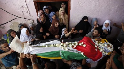 Palestinians carry the body of Jihad Aslan during his funeral at Qalandiya Refugee Camp near the West Bank city of Ramallah