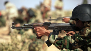 A trainee soldier from the Libyan army takes aim at a target during their graduation exam in Geminis