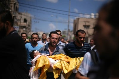 A Palestinian relative carries the body of four-year-old Qassim Elwan