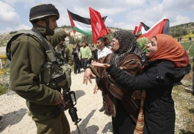 Israeli soldier gestures in front of Palestinian protesters during demonstration marking Land Day near Hebron