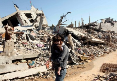 A Palestinian man carrying his son walks in front the rubble of houses which were destroyed during the recent Israeli offensive on Gaza Strip
