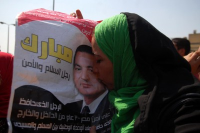 A supporter of Egypt's deposed autocrat Hosni Mubarak kisses a poster of him in front of Torah Prison