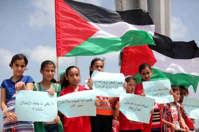 Palestinians children hold placards and wave their national flag during a rally to show support for activists aboard a flotilla of boats who are soon to set sail for Gaza in a fresh bid to break Israel's blockade of the territory