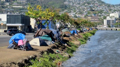 In this Thursday, June 11, 2015 photo, homeless people and their tents line a canal in Honolulu. Hours after a city crew cleared the banks of the canal, the homeless people that had been living there moved right back to the riverside, leaving some wondering whether the expense of taxpayer money was justified. (AP Photo/Cathy Bussewitz)