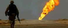 US ARMY SOLDIER WALKS TOWARDS BURNING OIL WELL IN SOUTHERN IRAQ