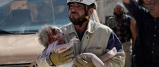 """A civil defense member carries an injured baby who was pulled out from under debris in Syria. 