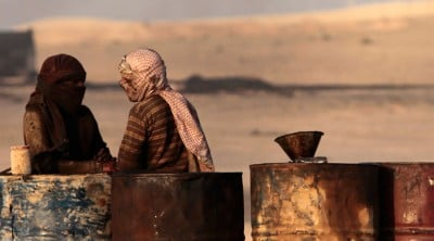People talk as they stand next to oil barrels at a makeshift oil refinery site in al-Mansoura village in Raqqa's countryside © Hamid Khatib / Reuters