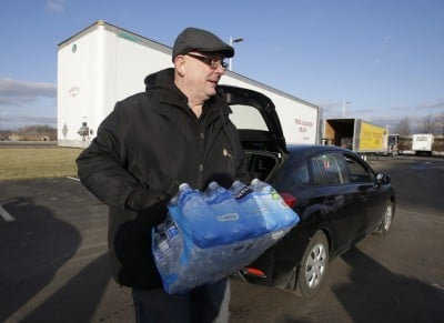 John Whitaker, executive director of Midwest Food Bank, carries a case of water that was donated to Flint residents on January 27. CREDIT: AP Photo/Darron Cummings