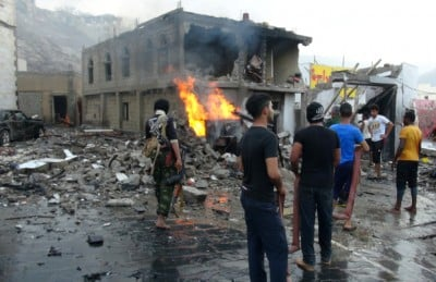 Bystanders look on at the carnage following a suicide car bombing in the Yemeni city of Aden (AFP)
