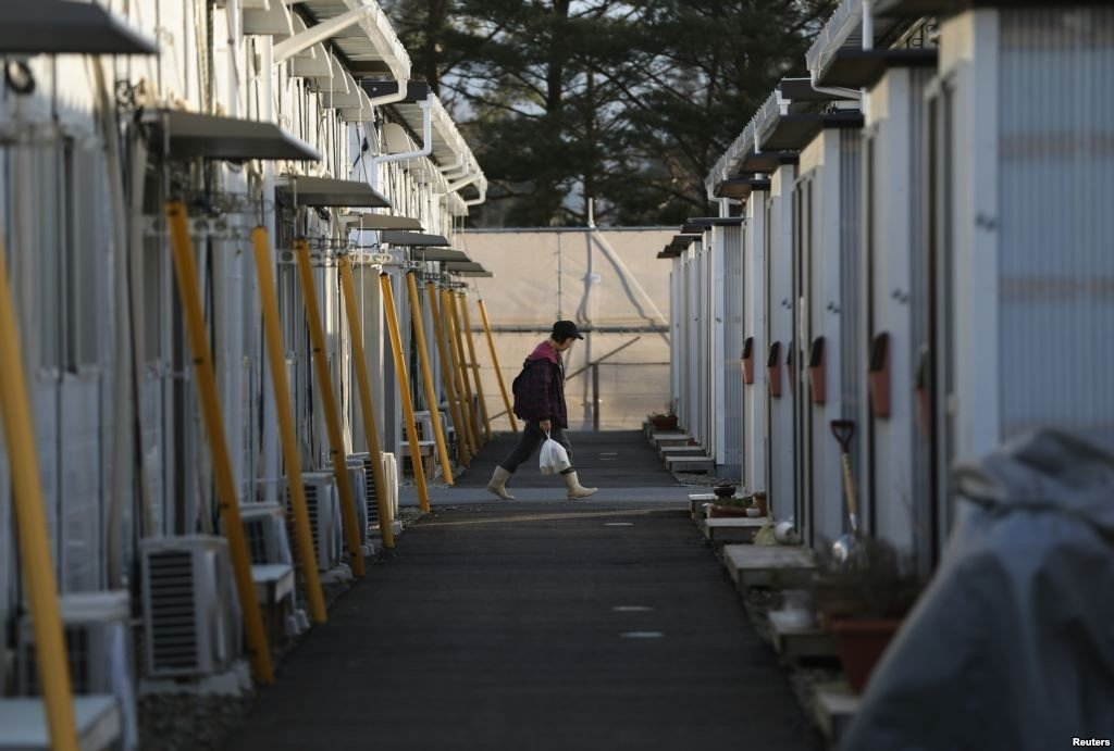 A woman walks in a temporary housing complex where evacuees from the Miyakoji area of Tamura are living, at Funahiki area in Tamura, Fukushima prefecture, April 1, 2014.(REUTERS/Issei Kato)