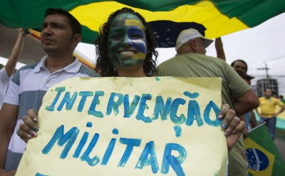 "Woman shows a placard reading ""Military intervention"" during a protest against Brazil's President Dilma Rousseff in Manaus"