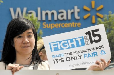 Photo of woman holding Fight for 15 sign outside of Walmart Supercentre