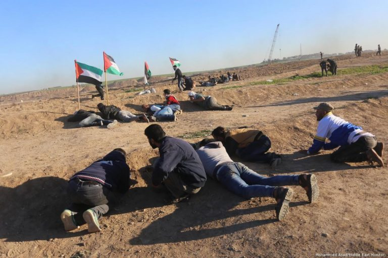 Palestinian take cover as Israeli forces fire at protesters at the Gaza border on 14 December 2018 [Mohammed Asad/Middle East Monitor]